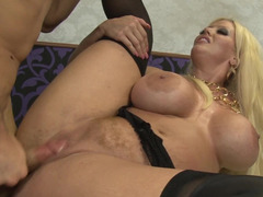 A blonde with big tits penetrates her lover by a strap on
