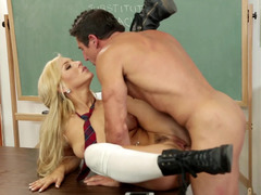 A corrupt schoolgirl is getting fucked on the desk by her teacher
