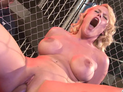 A nude blonde is getting fucked in the ring in a large cage