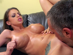A brunette that has huge tits is licking and riding a cock