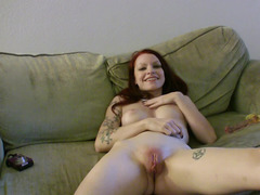 A redhead moans as she plays with her delicious pink pussy