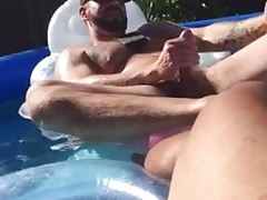 Two gays jerking together on pool