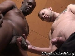 A black gay hunk allows a tattooed fairy to stroke and rub his BBC