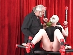 Shackled heavy lady in gas mask bound to bench with her depilated pink slit wide open