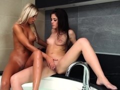 A blonde and a brunette take a sexy lesbian bath with one another