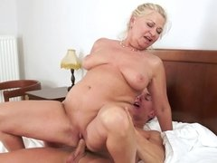 A fat old granny is getting her pussy penetrated on the white sheets