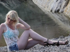 Bigtitted blonde displays her figure near the lake