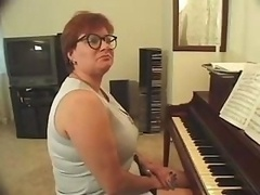Plump piano teacher busted getting skewered with a pair of purple poles
