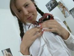 A busty schoolgirl is removing her clothes an sitting on the desk