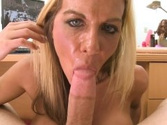 Blonde cougar is giving a guy a blow job next to the lens here