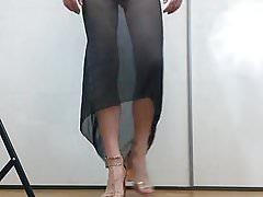 Boy walking in high-heels wearing a delicate black dress.