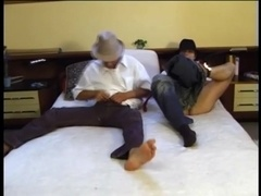 Two gays wearing hats and shirts fuck in cowboy position in a bedroom
