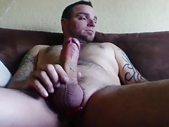 Muscular tattooed stroking a very fat dick