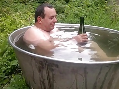 Naked old man rolls around in outside bath tub.
