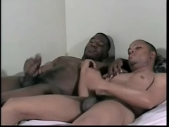 Two black gays enjoy jerking their weiners off in a bedroom