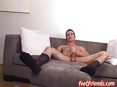 A tall hunk is jerking his cut cock while playing with socks