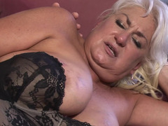 A fat blond granny is getting fucked by a young man on the sofa