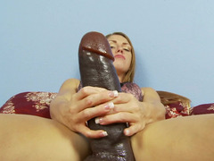 A sexy thing is pushing a huge dildo into her meaty and sexy cunt