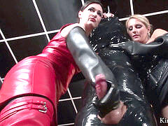 mistress in red hip high boots and her collegue do some gloved milking
