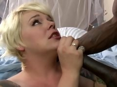 A blonde with short hair really likes black boys to ram her