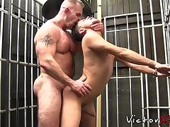 Muscular daddy lets bottom out of cage for bareback