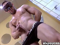 Masked muscular dude passionately strips and jacks off