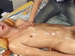 Twink lies back while his hard cock is oiled and brought to orgasm