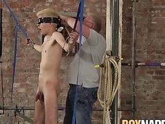 Blindfolded blonde twink oiled up to have his dick stroked